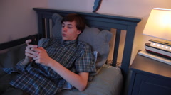 Teenage boy sitting in bed, resting, holding smartphone, bedtime Stock Footage