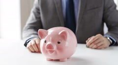 Close up of man putting money into piggy bank Stock Footage