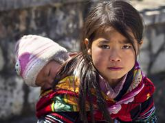 Unidentified Hmong Girl Carrying Baby in Sapa Town, Vietnam Stock Photos