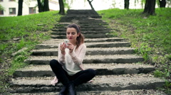 Woman sitting on the stairs in park and improving makeup Stock Footage