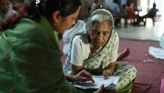 Volunteer teaches an old Indian woman literacy. Stock Footage