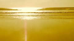 Gold slow motion ocean with smooth, flat, sunlit beach. Stock Footage