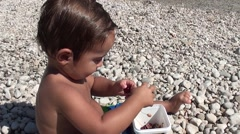 Toddler tries to remove a pip from a cherry 2 Stock Footage