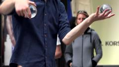 Street artist with glass balls - people watch him - closeup Stock Footage
