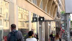 Urban street with walking people - detail of brand Apple on the building Stock Footage