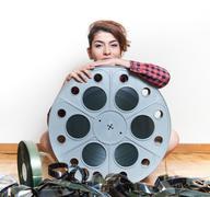 Young woman sitting behind big cinema movie reel Stock Photos