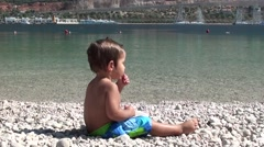 Toddler turns and looks into camera on the beach Stock Footage