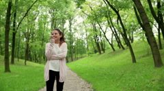 Woman standing in the park and talking on loudspeaker - stock footage