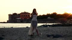 Beautiful female model posing in front of castle and ocean at sunset Stock Footage