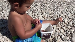 Wet toddler removing pips from cherries on the beach Stock Footage