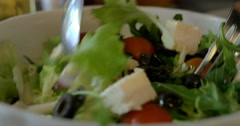 Tossing Greek salad before eating Stock Footage