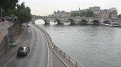 Motion in Paris cars drive in Ile de la Cite, bridge Pont Neuf, Seine flow slow  - stock footage