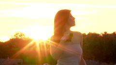 Gorgeous lady playing with long silky black hair in front of sunset Stock Footage