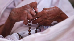 Hands of an old woman disfigured by paralysis, sorted out the rosary. Stock Footage