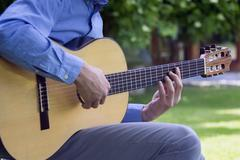 Young male playing a classic guitar outside - stock photo