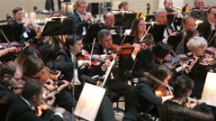 A group of violinists in the orchestra during a symphony concert. - stock footage