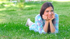 Beautiful smiling girl lying on a grass outdoor. Stock Footage