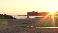 Stock Video Footage of Wide shot of woman in front of sea and castle at sunset posing