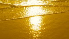 Slow motion sparkling ocean in gold with detail of sparkling water and sand. - stock footage