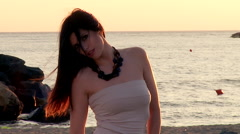 Beautiful female model looking camera posing in front of ocean at sunset - stock footage