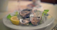 Pouring lemon juice on oysters - stock footage