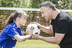 Teenager girl with his father play soccer in a beautiful day Stock Photos