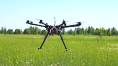 Flying heavy quadrocopters over green field Stock Footage