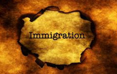Immigration text on burning paper hole Stock Photos
