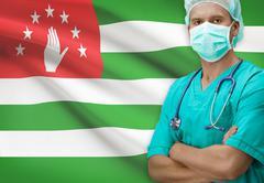 Surgeon with flag on background - Abkhazia - stock photo