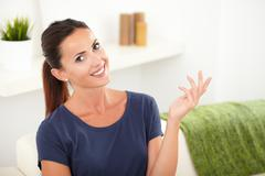 Cheerful woman smiling at the camera while holding one hand raised Stock Photos
