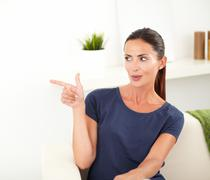 Cheerful woman pointing while looking away from the camera - copy space - stock photo
