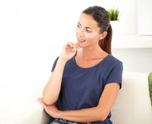Smiling woman looking away from the camera while wondering with one hand on h - stock photo