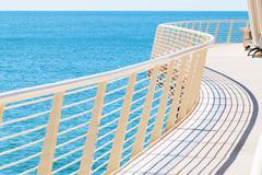 curved metal railing of Lido di Camaiore's pier - stock photo