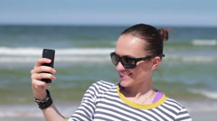 Young woman taking a self-portrait with her smartphone on sea background HD Stock Footage