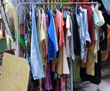 Used second hand summer clothes on flea market Stock Photos