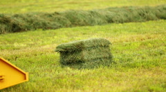 Farming tractor loads hay bale Stock Footage