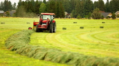 Red tractor bales hay in field Stock Footage