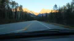 Driving through Rocky Mountains with trucks, BC, Canada. Alpenglow. Stock Footage