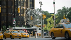 Many taxis driving past famous globe at Columbus Circle - yellow cabs in NYC Stock Footage