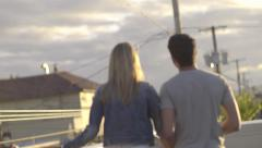 Cute Couple Walk To Edge Of Rooftop To Get A View Of City Below And Take Photo Stock Footage