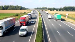 Many cars and trucks use a german freeway ,,Autobahn,, with some wind turbines Stock Footage