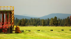 Farming tractor loads bales of hay - stock footage