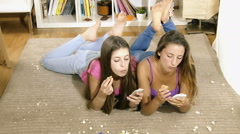 Two friends texting and playing with phone laying on floor at home  with all Stock Footage