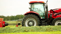 Red tractor bales hay in field, side view Stock Footage