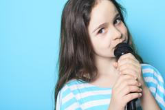 Girl sing in a microphone Stock Photos