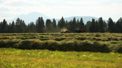 Tractor bales hay with scenic mountains in background - stock footage