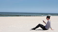 Girl reading or writing sms on her mobile smartphone on sea background HD Stock Footage