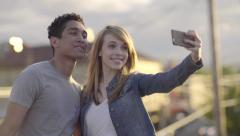Cute Couple Take Silly Selfies On A Rooftop At Sunset In The City (4K) Stock Footage