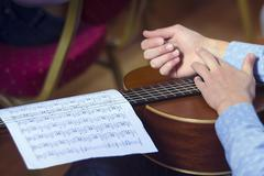 Young male's hands and guitar with musical scores - stock photo