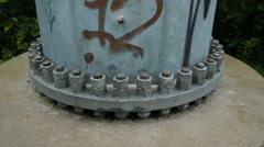 Big nuts and bolts securing base of pole. Handheld shot. - stock footage
